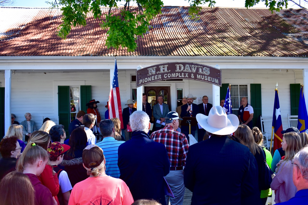Crowd listening to the history of the Lake Creek Settlement in front of the Nat Hart Davis Cottage.