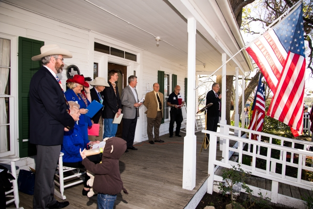 Ceremony begins with speeches from the porch of the Nat Hart Davis Cottage.